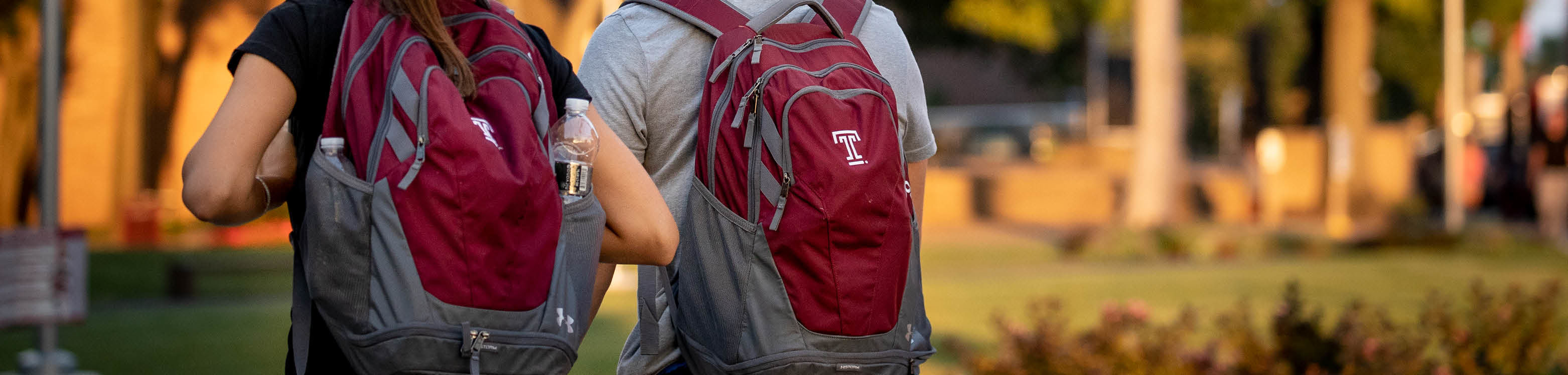 2 students walking on campus, close up of their Temple T backpacks