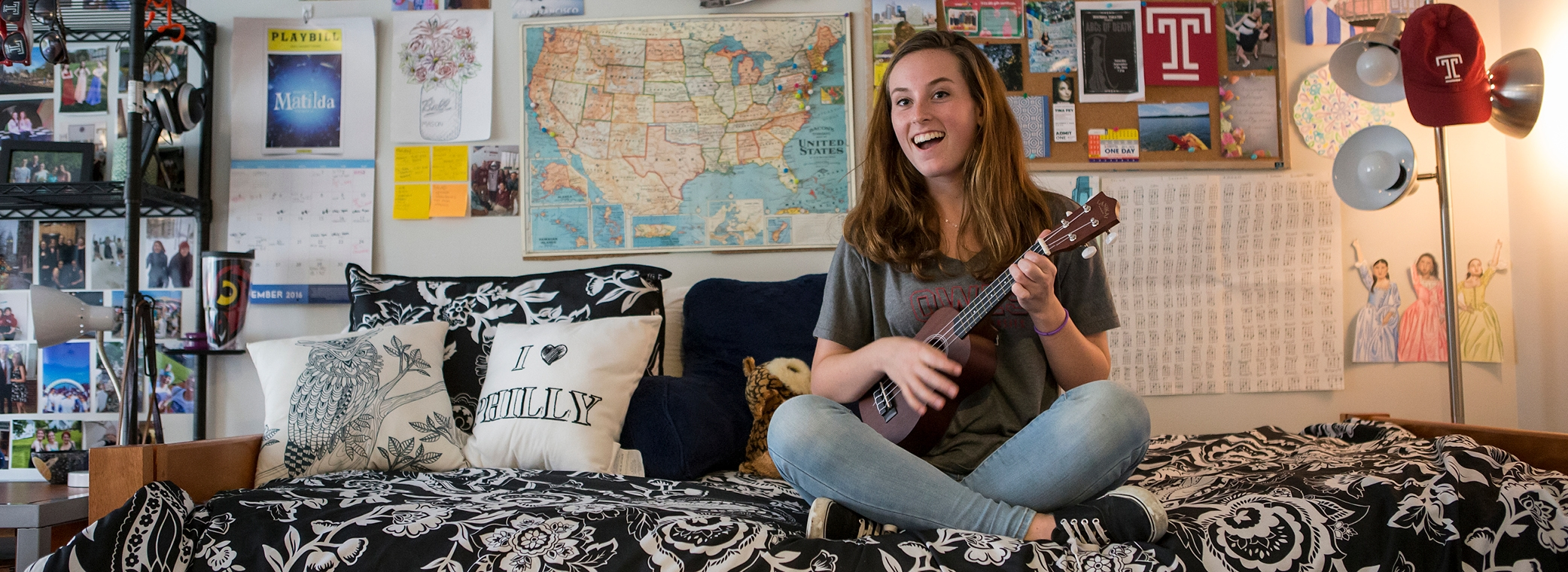 Female Temple student on her bed in her room playing a guitar